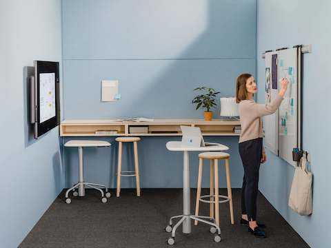 Woman in a small room with a smart board, pinning project work on a board attached to a wall.