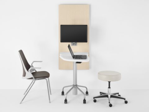 A side chair and stool on either side of small interaction peninsula formed by the Intent Solution table and wall unit.