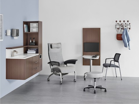 An exam room with Mora System casework in a dark brown finish and an Intent Solution table between a patient chair and side chair.