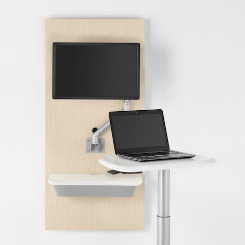 An Intent Solution technology support wall unit in an ash wood finish with an Intent Solution mobile, height-adjustable table.
