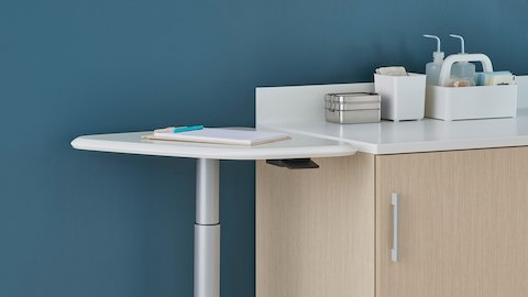 An Intent Solution height-adjustable mobile technology table with a white surface and silver base next to Mora System casework in a light wood finish and Corian surface.