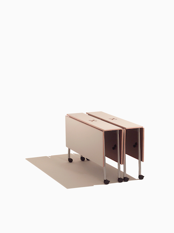 Two beige Intersect Tables, nestled together in the folded position. Select to go to the Intersect Tables product page.