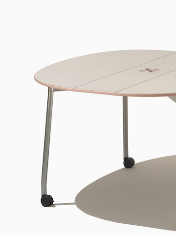 A round Intersect Table with a beige top. Select to go to the Intersect Tables product page.