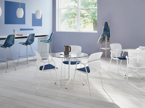 Break room featuring white Keyn side chairs with blue seats and blue Eames Molded Fibreglass stools.