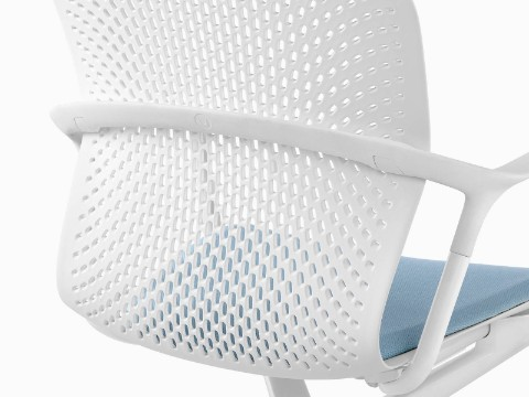 Close view of the perforated back on a white Keyn side chair.