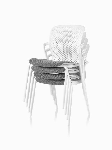 White Keyn side chairs with gray fabric seats, stacked four high.