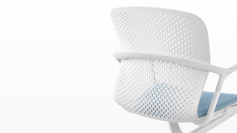 White Keyn side chair with a blue fabric seat, viewed from the rear and showing the one-piece perforated shell.