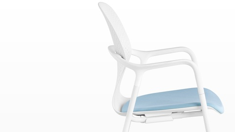 Profile view of a white Keyn side chair with a blue fabric seat.