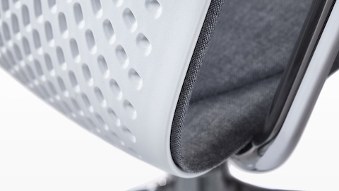 Close-up of the one-piece perforated shell on a white Keyn side chair.