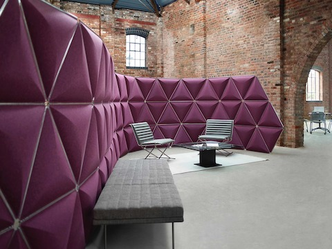 Triangular Kivo tiles in magenta fabric divide space in a brick-walled open workplace.