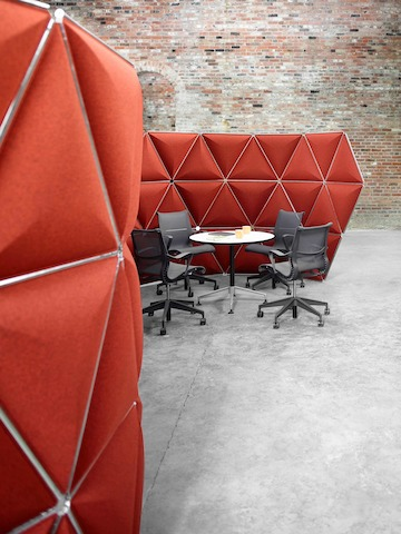 Triangular Kivo tiles in red fabric form a serpentine configuration that houses a small meeting space.