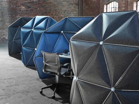Triangular Kivo tiles in shades of blue and gray form a row of four small workstations.