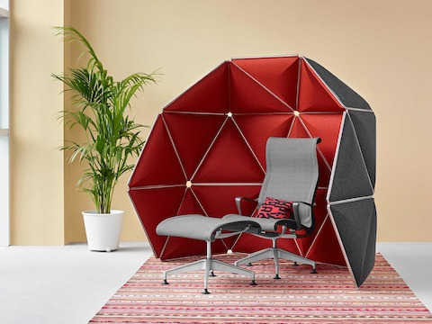 Triangular Kivo tiles in red fabric define a small, partially enclosed retreat containing a gray Setu Lounge Chair and Ottoman.