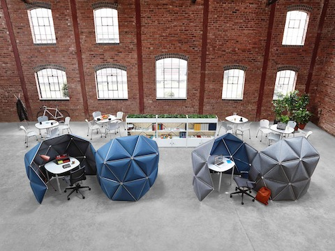 Overhead view of a brick-walled open office containing four Kivo workstations with blue and gray tiles.