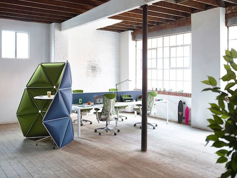 Blue and green Kivo tiles define a small interaction area next to a benching workspace supported by green Embody office chairs.