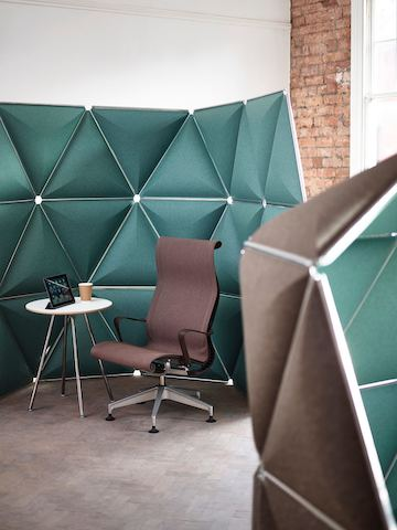 Triangular Kivo tiles in green fabric define a partially enclosed retreat containing a small table and Setu Lounge Chair.