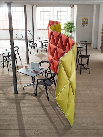 Red and yellow Kivo tiles create a serpentine space divider in an open workplace.