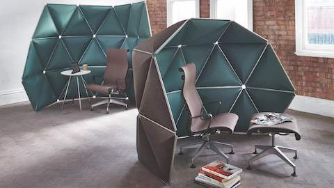 Triangular Kivo tiles in green fabric form two small retreats in a brick-walled work area.