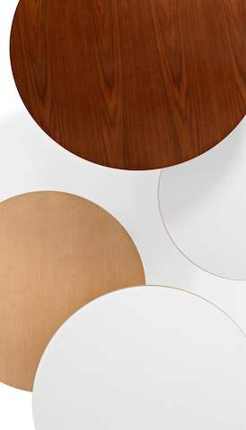 Overhead view of four round tabletops in various finishes. Select to go to the Herman Miller tables landing page.