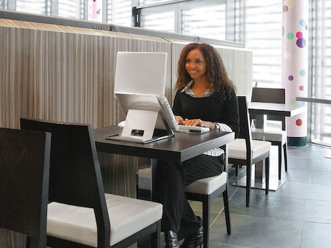 A woman works in a break area with her notebook computer positioned at eye level thanks to Lapjack Mobile Technology Support.