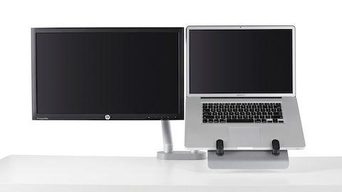 A dual monitor arm lifts both a computer screen and notebook computer, using a laptop mount, off the work surface.