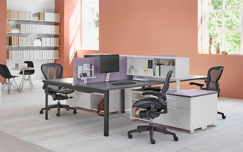 Four gray Mirra 2 Chairs at Layout Studio bench workstations with a wood desk top and white storage units and bookshelves.