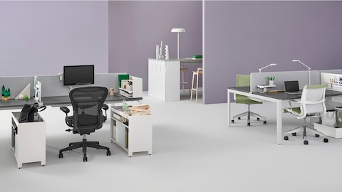 Individual Layout Studio individual workstations with Black Aeron Chairs and green upholstered Setu Chairs, with personal items and task lighting.