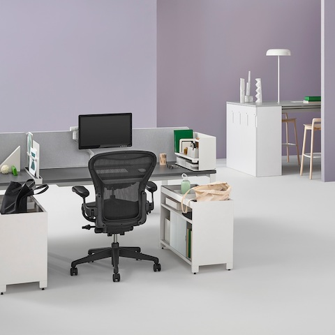 An office setting with two Layout Studio benches with gray fabric center privacy screens, Ubi Work Tools, Tu credenzas, and Aeron and Setu Chairs.