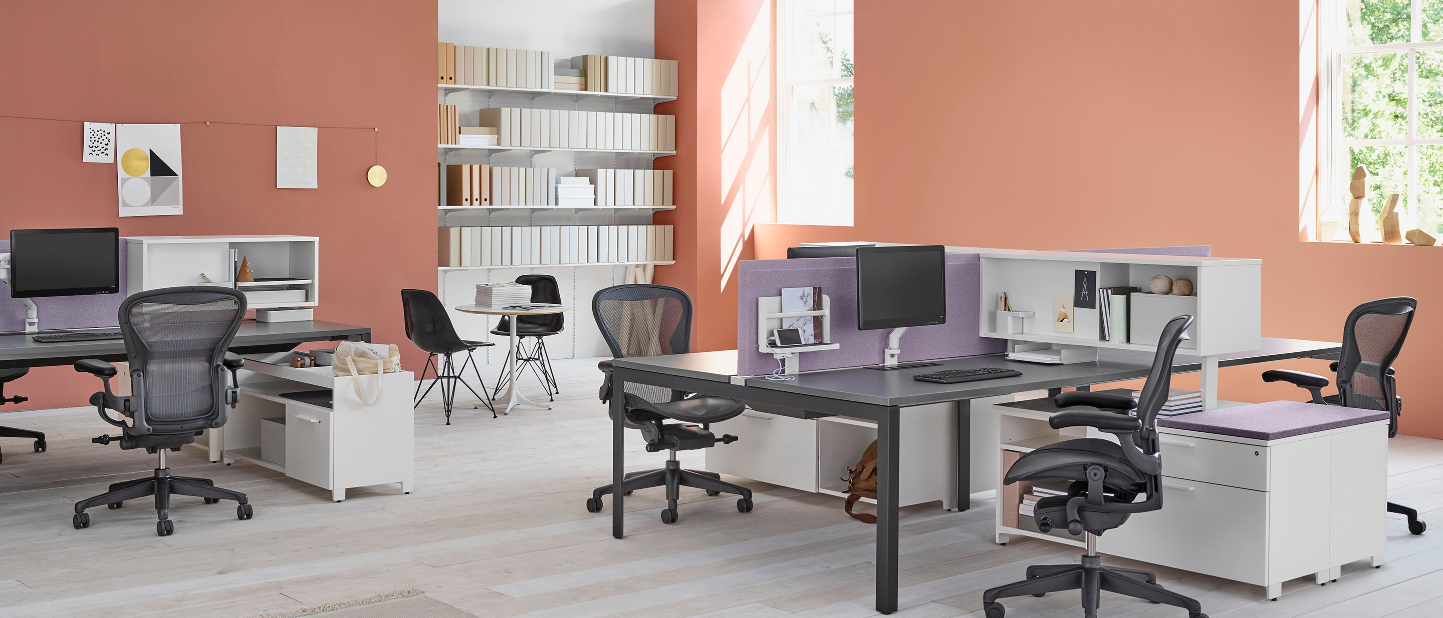 A workspace setting with two Layout Studio benches with purple fabric center privacy screens, Aeron Chairs, Tu Storage cubbies, and Tu credenzas.