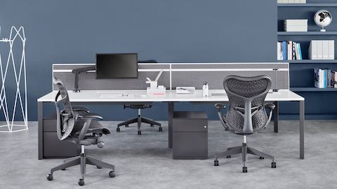 Four-person Layout Studio bench with a grey divider screen, two black Mirra 2 chairs, and under-desk storage.