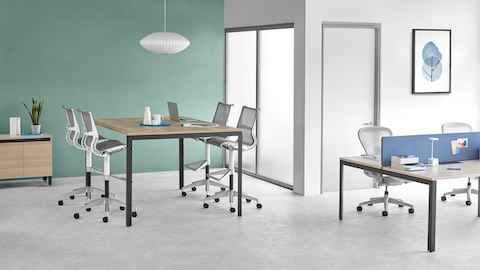 Office setting with a Layout Studio standing-height table and light grey Setu Stools, adjacent to a Layout Studio bench with a blue divider screen and light grey Aeron chairs.
