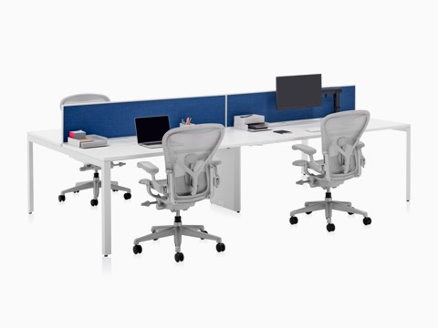 A four-person Layout Studio bench with a blue divider screen, work tools and three light grey Aeron Chairs.