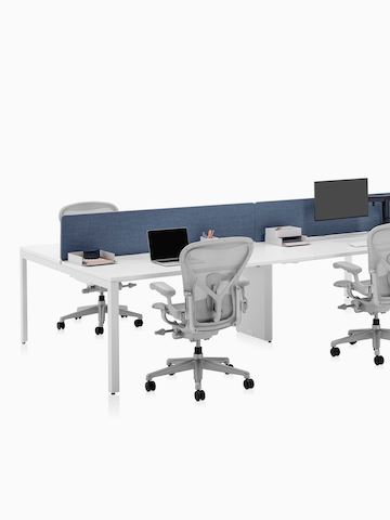 A four-person Layout Studio bench with denim blue divider screen, work tools, and three light grey Aeron Chairs.