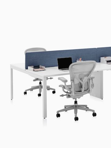 A four-person Layout Studio bench with denim blue divider screen, work tools, and three light grey Aeron Chairs. Select to go to the Layout Studio product page.