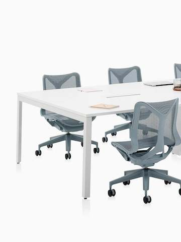 Six-person Layout Studio meeting table with gray low-back Cosm Chairs. Select to go to the Layout Studio product page.