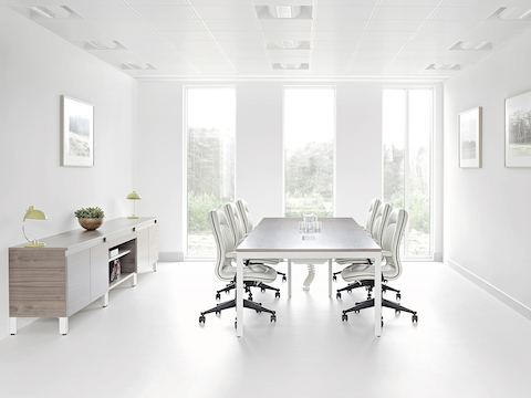 Natural light flows through a conference room equipped with a Layout Studio table, credenza, and white leather chairs.