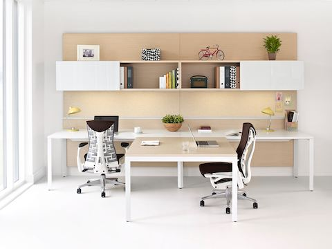 Two Layout Studio workstations with a shared work surface, overhead storage, and brown Embody office chairs.