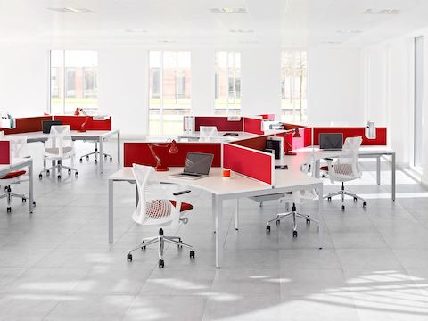 An open office featuring curved Layout Studio work surfaces with red privacy screens and white Sayl office chairs with red seats.