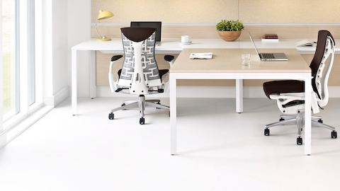 Two Layout Studio workstations with a shared work surface and brown Embody office chairs.