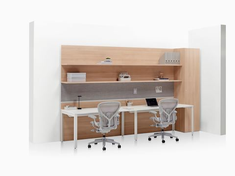 Layout Workwall with open shelves, two Layout Studio desks, wardrobe, and two light grey Aeron Chairs.