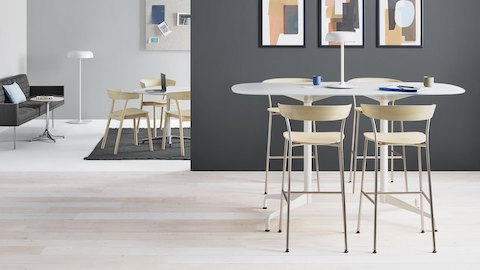 Four Leeway Stools with metal bases and light wood seats and backs at a standing height table near a lounge with a black sofa and chairs at a table.