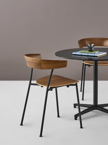 Two Leeway Chairs with black metal bases and dark wood seats and backs at a black Saiba table with a coffee cup and notebooks on top.