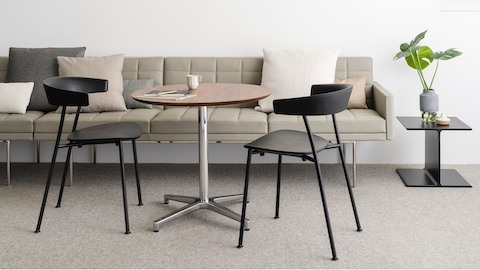 An informal meeting space featuring a tan Tuxedo Component sofa, a round Saiba occasional table, and two black Leeway side chairs.