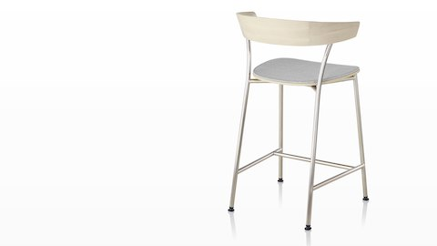 A Leeway Stool with light metal base, light wood backrest, and upholstered seat, viewed from the rear.