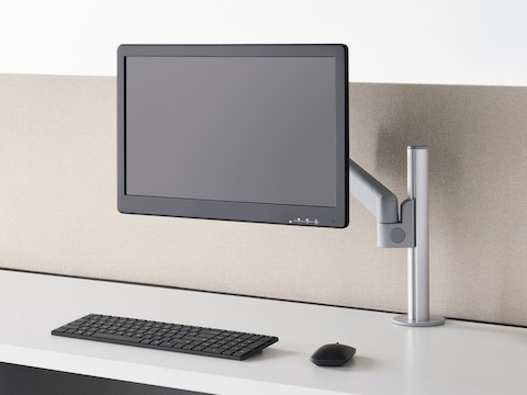 Three-quarter front view of a grey Lima Monitor Arm, on a sit-to-stand desk with a monitor and keyboard.