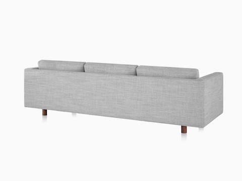 A Lispenard sofa with walnut wood legs and gray upholstery, viewed from the back at an angle.