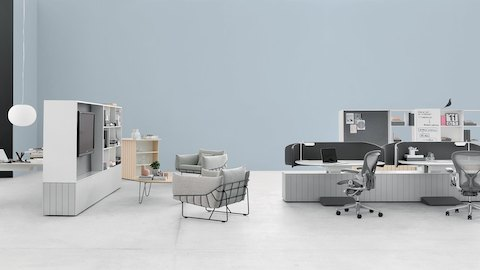 A set of Locale workstations with gray Aeron office chairs near a collaborative lounge space with Locale Storage and gray Wireframe Lounge Chairs.