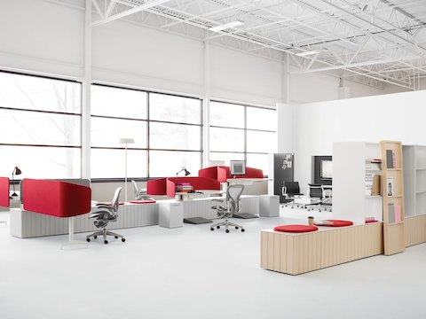 An open office in an industrial building with gray Aeron Chairs at height-adjustable workstations that have red fabric privacy screens.