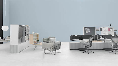 Two gray Wireframe lounge chairs at a Locale lounge meeting space near a group of Locale sit-to-stand workstations with gray Aeron Chairs.