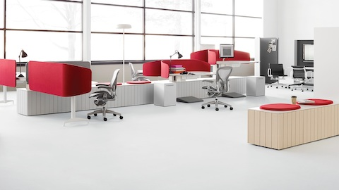 A group of Locale workstations with red fabric privacy screens in an open office with gray Aeron office chairs and integrated Locale storage.